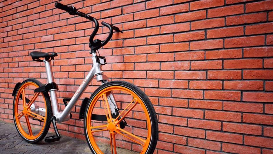 bici appoggiata al muro con logo Mobike