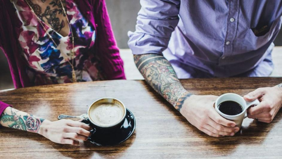 coppia con tatuaggi sul braccio mentre prende il caffè